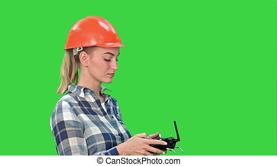 Female engineer operating a drone analyzing object on a Green Screen, Chroma Key.