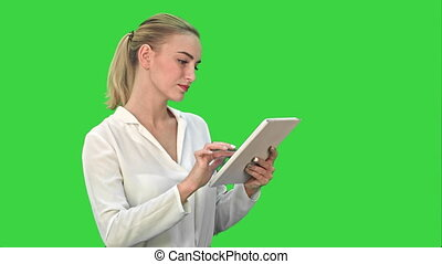 Concentrated businesswoman standing with digital tablet on a...