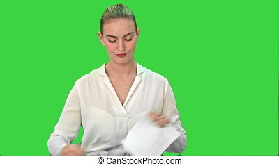 Young woman in anger rips a sheet of paper, throw it at the camera on a Green Screen, Chroma Key.