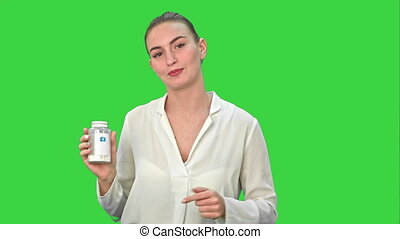 Pretty woman describing and advertising pills for the camera on a Green Screen, Chroma Key.