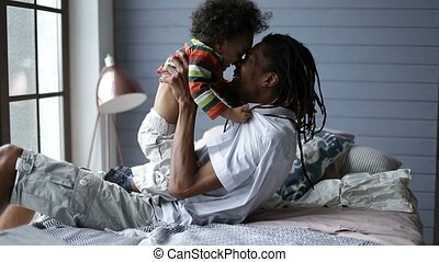 Smiling father playing with happy son at home