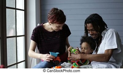 Smiling mixed race family playing with toys - Cheerful...