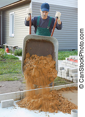 Preparation for a paving - The worker prepares a place for a...
