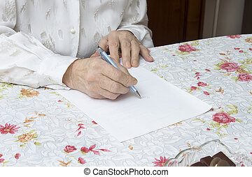 Hands of the old woman who writes handwritten testament on a...