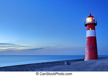Red and white lighthouse and a clear sky at dusk