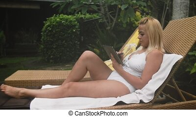 Blonde in the swimsuit lies on the lounger with the tablet -...