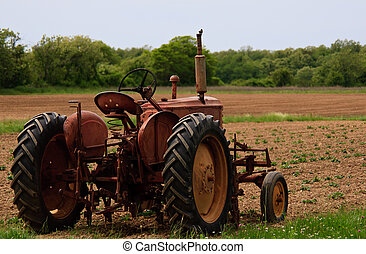 Old farm tractor in the field - Old red rusty farm tractor...
