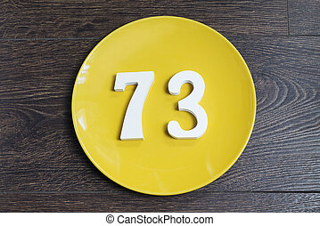 The number seventy-three on the yellow plate. - The number...
