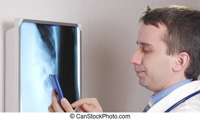 A young doctor uses a phone in the clinic. A man records the results of a patient's x-ray.