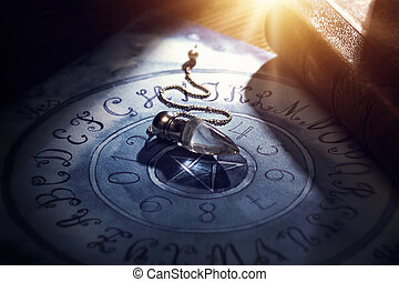Crystal pendulum on a board - Foretelling the future with...