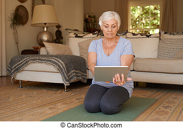 Senior woman practising yoga with a digital tablet at home -...