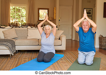 Active senior couple practising yoga together in their living room