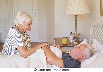 Senior woman taking care of her sick husband in bed - Sick...