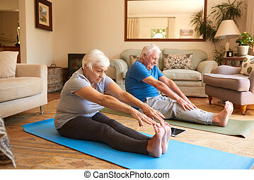 Active senior couple stretching together while doing yoga at home