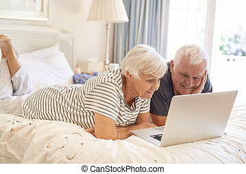 Happy senior couple lying on their bed using a laptop -...