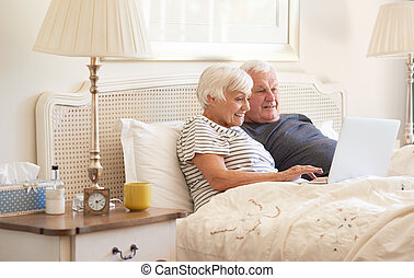 Seniors using a laptop on their bed in the morning - Smiling...