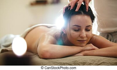 Massage parlor - young woman gets relaxing healing therapy...