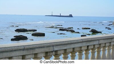 Lighthouse in the distance, sea with rocks, Balcony with sea...