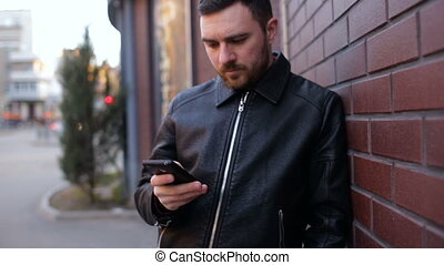 Young man using smartphone standing by brick wall in city