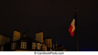 French flag waving in the wind near house in the night sky background