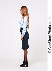 Full body profile view of of young business woman on gray...