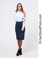 Full body studio shot of young business woman on gray...