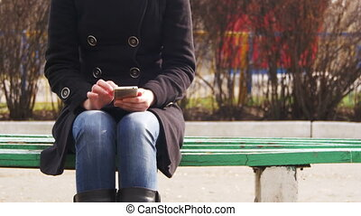 Young Girl using a Mobile Phone on a Bench in the City Park...