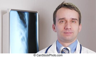A young doctor looks at the camera and smiles. Against the background hanging x-ray of the patient. Shirt with a tie and a stethoscope on the neck