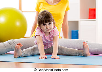 Mother and daughter kid doing sport exercises. Child bending...