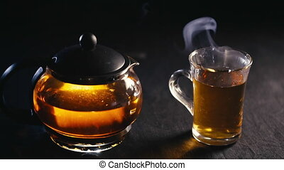 black tea in a transparent teapot tea in glass Cup on black background