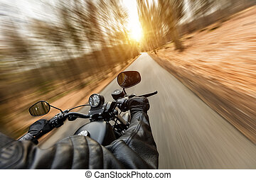 Close-up of motorbiker riding on empty road in forest with...