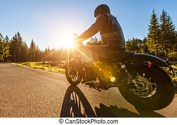 Dark motorbiker riding high power motorbike in nature with...