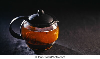 black tea in a transparent teapot on a black background