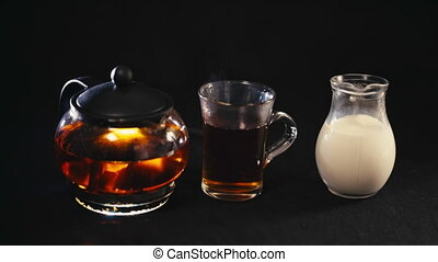 milk pouring into tea in a transparent Cup