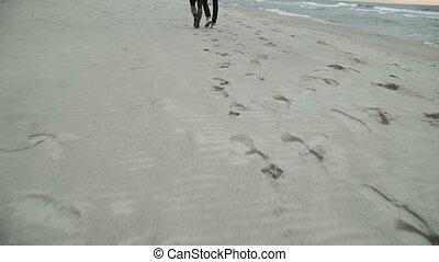 Footprints in the sand, Young couple looking at the sea, walking the beach, coat and hat, Baltic or Iceland cold weather