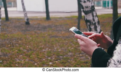 Young Girl using a Mobile Phone in the City Park
