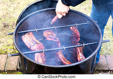Man roasted barbecue smoke spare ribs in 200 liter fuel tank