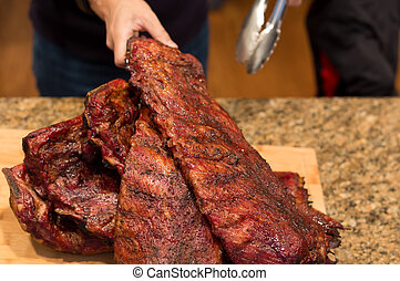 Man hand holding spare ribs on wooden board on family dinner...