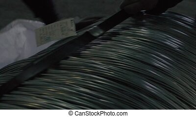 Man's hands wheeling the metal wire roll, close up, 4K
