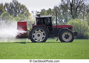 tractor spraying a filed with pesticidesfertilizers