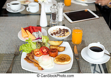 Breakfast set on the tabla with pancakes, bacon, eggs and...