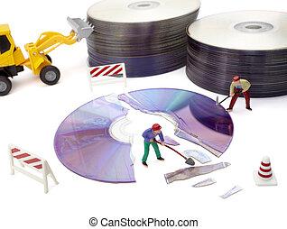 miniature toy workers repairing computer broken compact disk...