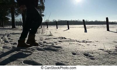 Man legs kicking snow in the daytime.