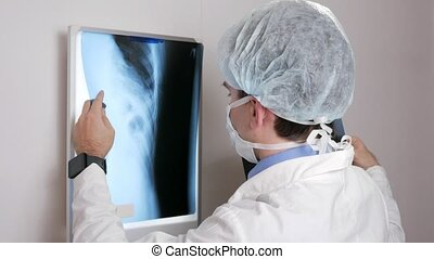 A young doctor examines the results of a patient's X-ray on the wall. Analyzes of the thorax and ribs.
