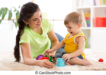 kid boy and mother play together with cup toys
