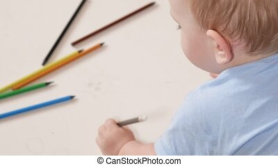 An attractive boy 2 years old draws in colorful pencils at home. It is black in the hand.