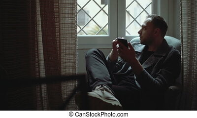 Stylish man sitting in armchair and looking at window. Young...