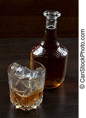 Glass whiskey on dark four - Glass and bottle whiskey on...