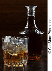 Glass whiskey on dark three - Glass and bottle whiskey on...