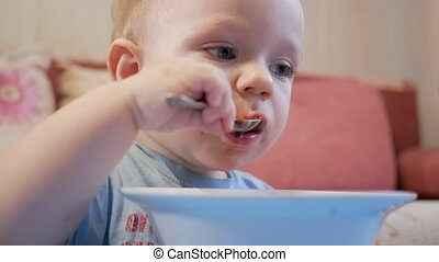 An attractive boy 2 years old is eating red soup himself. Spoon and hands flowing liquid. The concept of healthy eating of children.